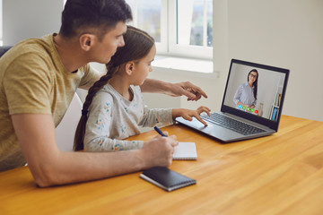 Online learning lessons education school. Father and daughter are doing online education with a teacher using a laptop sitting at home.