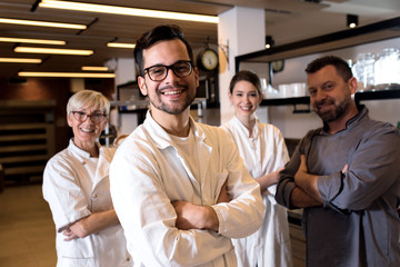 Portrait of young male baker at bakery with his colleagues in backgrounds.