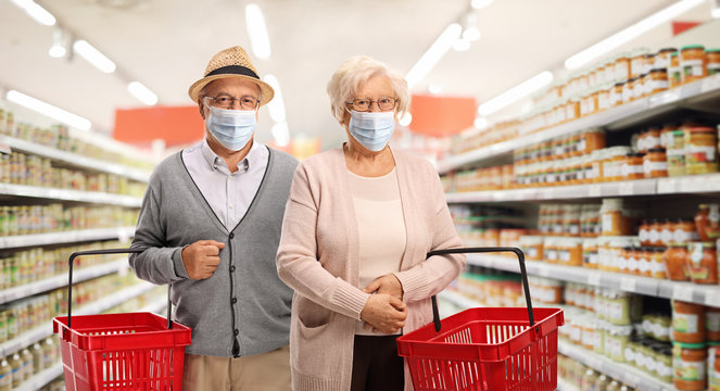 Elderly couple shopping in a supermarket and wearing medical masks
