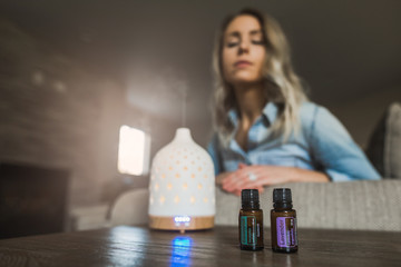 Young woman smelling her essential oil diffuser