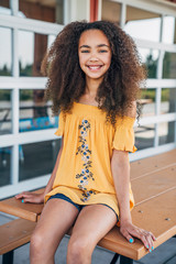 Portrait of smiling pretty girl in yellow dress with big curly hair
