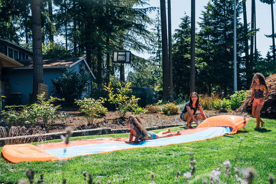 Girls playing on slip and slide in front yard of home