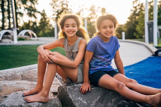 Portrait of smiling sisters outside in park at sunset