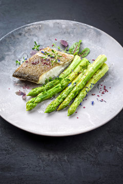 Fried gourmet skrei cod fish filet with green asparagus and lettuce offered as closeup on a modern design plate with copy space