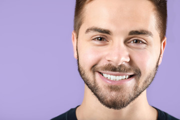 Fotomurales - Handsome smiling young man on color background
