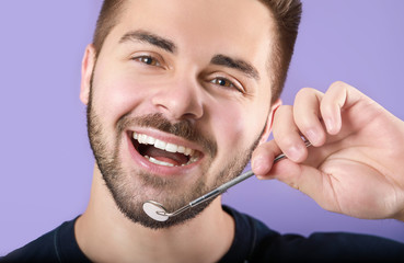 Fotomurales - Happy smiling young man with dental mirror on color background