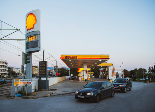 Athens, Greece - Mar 28, 2016: Modern Shell gas station with cars and customers illuminated at dusk in on of the neighborhoods of Athens near the port