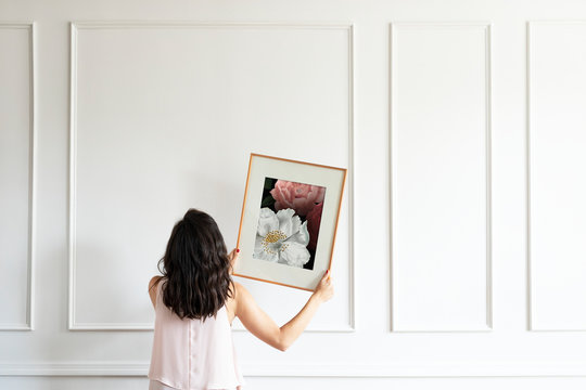 Woman hanging a frame on a white wall