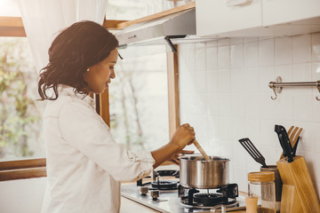 African American Black woman cooking boiling soup in the kitchen at home.