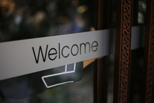 Close-up Of Welcome Sign On Glass Door