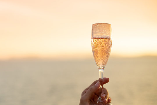Woman on yacht hold a glass of sparkling wine in her hand with background of golden sunset moment to celebrate her life and happiness.