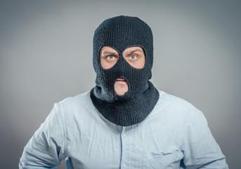 Face of a angry burglar wearing a black ski mask or balaclava - fototapety na wymiar
