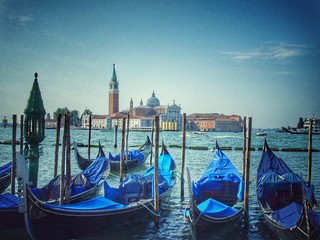 Boats Moored In Venice Against Blue Sky