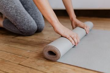 Foto op Textielframe School de yoga Woman rolling yoga mat