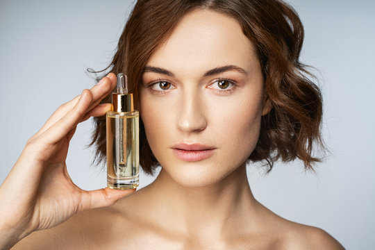 Calm beautiful woman holding cosmetic face serum