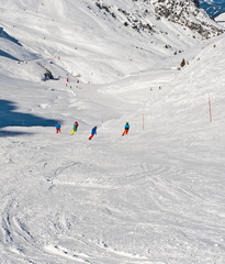 Fototapete - View of a ski slope in alpine winter resort with skiers