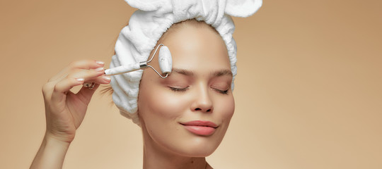 Beautiful girl makes a facial massage gua sha jade quartz roller, for the effect of skin rejuvenation. Procedure at home