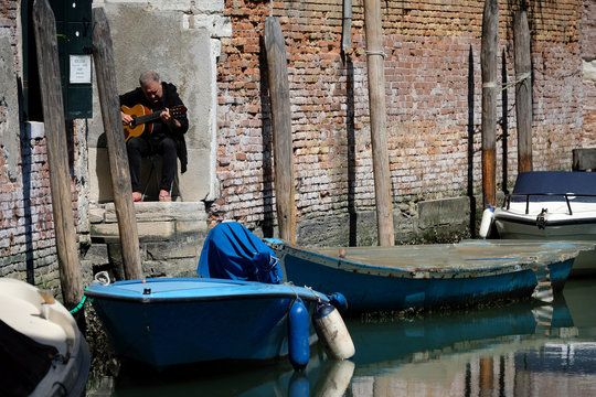 A man plays the guitar outside his apartment as Italy remains on lockdown due to a spread of the coronavirus disease (COVID-19) in Venice