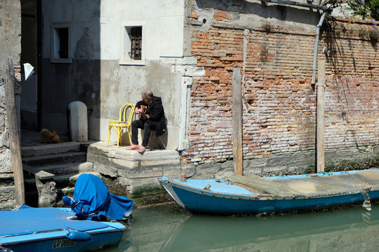 A man plays the guitar outside his apartment next to a deserted canal as Italy remains on lockdown due to a spread of the coronavirus disease (COVID-19) in Venice