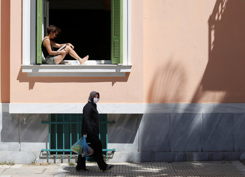A woman reads as she sits in a window as another woman carries bags after shopping at an open market following the coronavirus disease outbreak (COVID-19) ahead of Greek Orthodox Easter in Athens