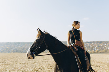 Portrait of jockey girl posing at nature, female horseback rider during hobby equestrian with black champion stallion animal. Overlooking wide open field and village Papier Peint