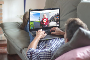 Man on the sofa using laptop with driving school online website on the screen Fototapete