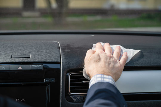 Middle age businessman in a blue suit cleaning front dashboard of a car using antivirus antibacterial wet wipe (napkin) for protect himself from bacteria and virus