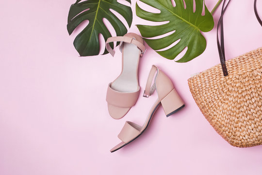 Monstera green leaves, women's sandals and straw bag. Flat lay, top view.
