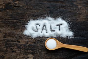 A pile of salt from salt shaker on wooden table, word salt, concept excessive salt intake.