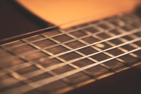 Close up shot of concert of frets and neck of an old classical concert guitar