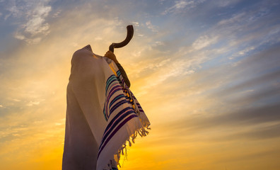 Blowing the Shofar - man in a tallith, Jewish prayer shawl is blowing the shofar ram's horn