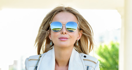 Outdoor fashion portrait of young pretty   blond woman in sunny day on street. Girl in sunglasses outdoor. Happy Fashion Woman in Sunglasses. Smiling Trendy Girl