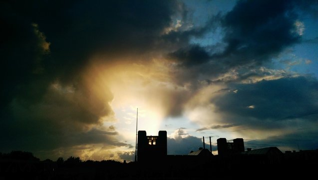 Low Angle View Of Silhouette Building Against Cloudy Sky