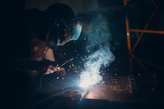 Welder welding metal construction on workshop