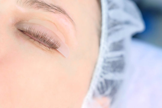 Woman's closed eye with bending lashes on curlers, lift eyelashes laminaton, closeup view. Making lash lifting in cosmetology clinic for young girl.