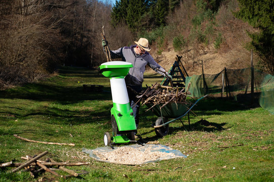 Gardener using electric shredder or wood chipper for shredding tree or shrub cuttings.