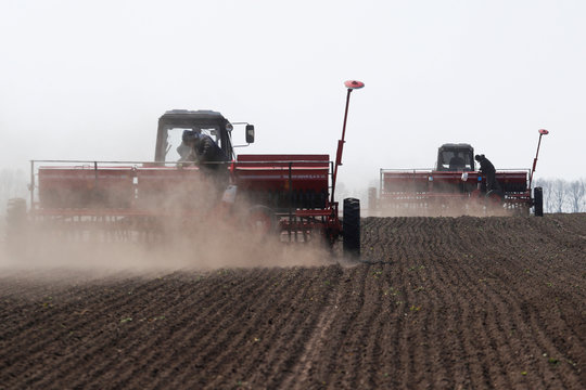 Agricultural workers control sowing machines as they plant soybeans in Kiev region