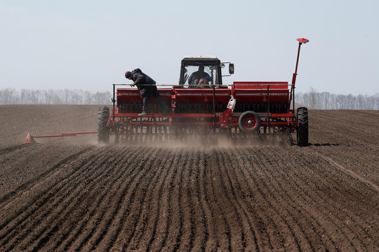 An agricultural worker controls a sowing machine during soybeans planting in Kiev region