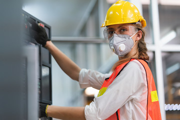 Female Engineer wear face mask with safety vest and yellow helmet operating control CNC Machinery at factory Industrial