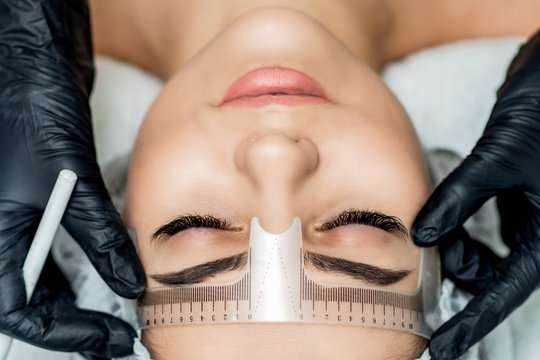 Top view markup with ruler on eyebrows of young woman during permanent make up.