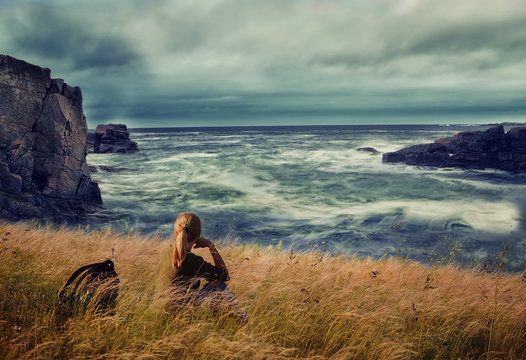 Girl traveler sits on a cliff by the ocean