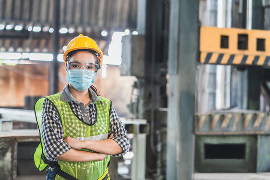 Asian female engineers wearing hygienic mask protect with helmet safety in factory Industrial.Coronavirus Protective, safety concept