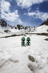 Fototapete - Pair of green snowshoes in snow. High snowy mountains and blue sky with clouds