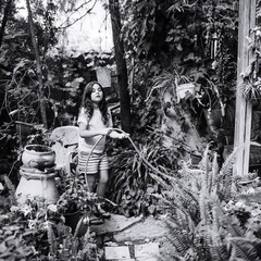 Tuinposter Begraafplaats Girl Watering Plants At Backyard