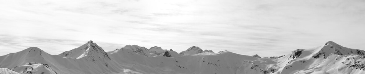 Fototapete - Panorama of high winter mountains with snowy slopes and sunlight cloudy sky