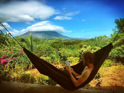 Shirtless Man Reading Book While Relaxing In Hammock Against Sky