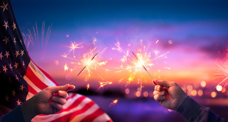 Fototapete - Usa Celebration - Hands Holding Sparklers And American Flag At Sunset With Fireworks