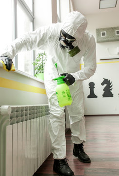 A man in protective equipment disinfects with a sprayer in the office. Surface treatment due to coronavirus covid-19 disease. A man in a white suit disinfects the room with a spray gun. Virus pandemic