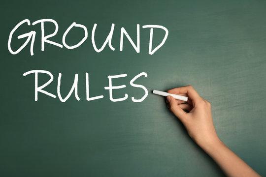 Woman writing phrase GROUND RULES on chalkboard, closeup