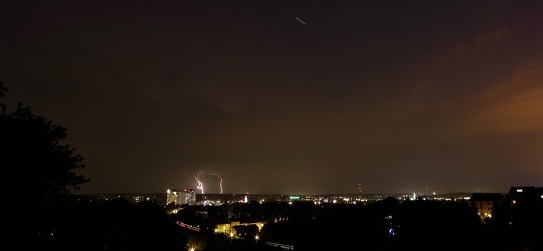 Distant View Of Lightening Over Illuminated City At Night